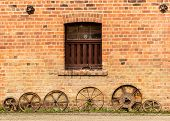 Row Of Old Rusty Cart Wheels Against Barn