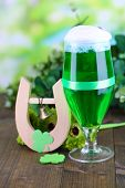Glass of green beer and horseshoe for St Patricks day on wooden table close-up