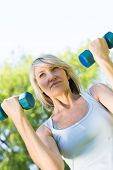 foto of lifting-off  - Tilt image of woman lifting dumbbells in the park - JPG