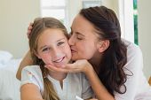 Loving mother kissing daughter at home