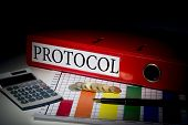 The word protocol on red business binder on a desk