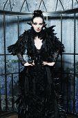Fashion model in fantasy dress posing in steel cage.