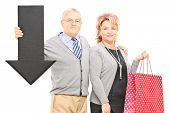 Mature couple holding shopping bags and big black arrow pointing down isolated on white background