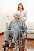 Smiling woman with her old senior father in a wheelchair at home