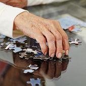 Old hand with wrinkles reaching for a jigsaw puzzle piece