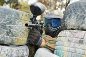 foto of paintball  - paintball player in protective uniform and mask aiming gun before shooting in summer - JPG