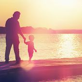 image of dock a lake  - Father and son walking out on a dock at sunset  - JPG