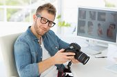 Handsome photographer holding his camera smiling at camera in creative office
