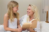 Happy mother and daughter with novel looking at each other in bed