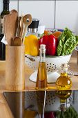 Cooking Spoon Rack, Vegetable, And Olive Oil On Worktop