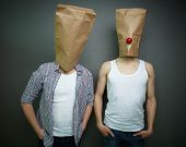 Two guys standing in front of camera in paper bags celebrating fool�?�¢??s day
