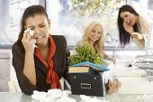 Fired young female office worker sitting at desk, crying, colleagues laughing at her at the backgrou