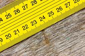 Yellow Ruler On A Wooden Background