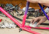 Hands of real bicycle mechanic sanding frame bike