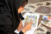 ESFAHAN, IRAN - DECEMBER 01, 2007:  Muslim woman artist in black headscarf paints traditional Persia