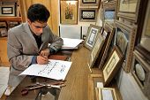 ESFAHAN, IRAN - DECEMBER 01, 2007:  Iranian calligraphy artist at work  traditional Persian art of decorative writing
