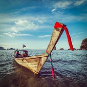 Vintage retro hipster style travel image of Thai Long tail boat on sunset, Krabi, Thailand