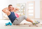 Happy attractive sporty handsome man doing sit ups exercises at home