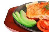 diet healthy food: hot grilled sea salmon fillet served on iron pan over wooden plate isolated on wh