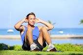 Man exercising sit-ups outside. Male fitness model training situps exercise outdoor in summer during