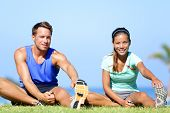 Stretching exercises - Fitness couple outside doing stretches exercise. Fit woman and man doing hams