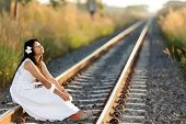 Beautiful young Thai woman meditating sitting in the last rays of the sun on a receding train track