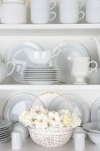 Vertical closeup of a  basket of roses on the shelf of a cupboard full of white plates. Items includ