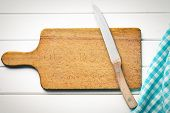 top view of cutting board with knife on white wooden table