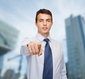 business and office, people concept - friendly young buisnessman pointing finger