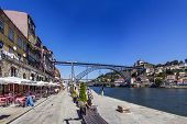 Porto, Portugal - July 27, 2013: Tourists and locals enjoy the Ribeira District scenery and summer s