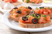 Delicious bruschetta with tomatoes on plate on table close-up