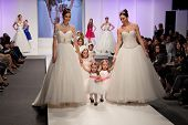 ZAGREB, CROATIA - FEBRUARY 15, 2014: Fashion models in wedding dresses with children models dressed