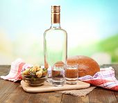 Composition with bottle of vodka and marinated vegetables on wooden table, on bright background