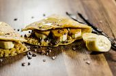 Closeup of banana pancakes wit choco chips on wooden table