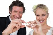 Happy bride and groom looking at wedding rings isolated over white background
