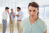 stock photo of half-dressed  - Colleagues gossiping with sad young businesswoman in foreground at a bright office - JPG