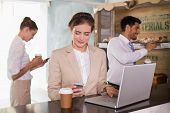 Businesswoman using mobile phone and laptop with colleagues behind in office cafeteria