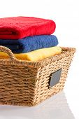 foto of cleanliness  - Colorful stack of fresh clean towels neatly folded in a wicker basket in red blue and yellow conceptual of cleanliness hygiene and housekeeping close up on a reflective white background - JPG