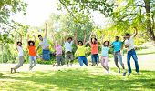 Group of excited multiethnic friends jumping in park