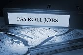 stock photo of payroll  - The word payroll jobs on blue business binder on a desk - JPG