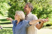 Happy couple standing with arms outstretched in park