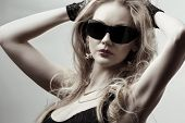 young gorgeous blonde wearing sunglasses posing in the studio