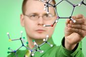 close up portrait of young chemist, developing new molecular structures. focus on molecule