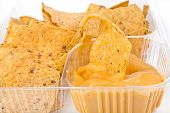 nachos chips with cheese sauce in plastic container isolated on white background