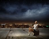 Young girl traveler sitting on bag at night