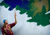 Young woman painting wall in colors with brush