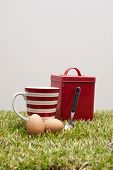 Red tin, coffee cup, two eggs and a spoon.
