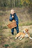 Happy Little Boy With Basket Full Of Mushrooms With The Dog On Forest Glade