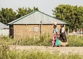 BOR, SOUTH SUDAN-NOVEMBER 1 2013: Unidentified women carry items through Bor, South Sudan.