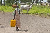 PANWEL, SOUTH SUDAN-JUNE 23 2012: Unidentified woman carries a large water jug to get water from the